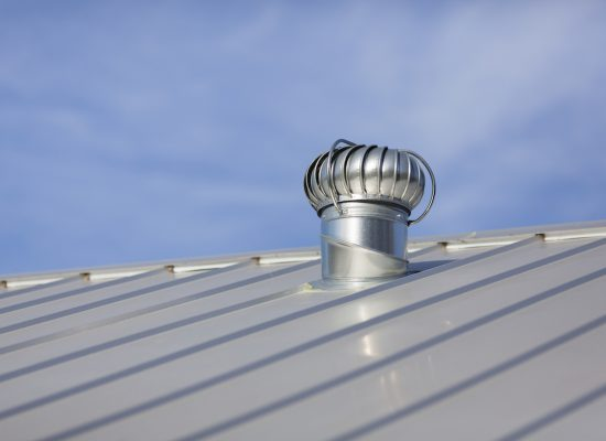 Stock photo of an attic vent on a freshly installed, brand new metal roof at a residential home.